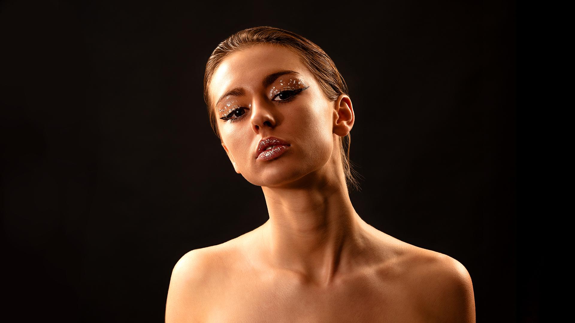 Modèle de femme sur fond noir avec un maquillage paillette, regardant l'objectif – photo portrait.